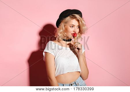 Horizontal studio shot of attractive woman holding a red lollipop close to her mouth.