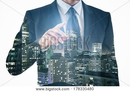 Close up of poiting businessman on night city background. Double exposure