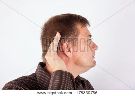 Man wearing hearing aid cupping his hand behind ear because he cant hear