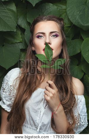 Portrait of a young woman with a delicate make-up she put a green leaf to her lips.