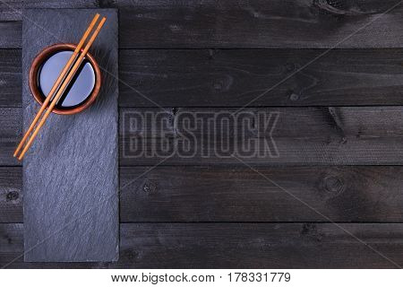 Background for sushi. Soy sauce, chopsticks on black table. Top view with copy space.