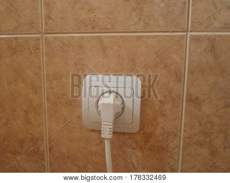 Electrical socket with cable connector on the tiled wall