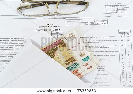 Glasses and an envelope with ruble bills lying on the sheet of accounting of working time. The calculation of remuneration. Russia