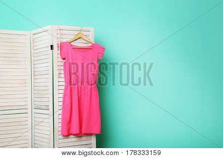 Pink Dress Hanging On Folding Screen On A Green Background