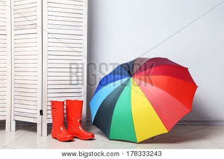 Red Boots With Umbrella Near Wooden Folding Screen On A Grey Background