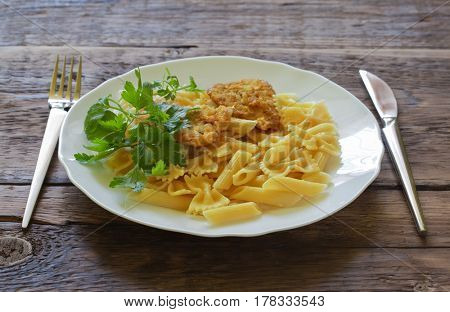 Pasta with meat on a plate with a fork and knife on a wooden background