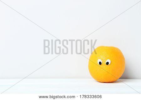Ripe Orange With Googly Eyes On Grey Background