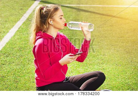 Thirsty young beautiful blonde hair fitness girl drinking water on the stadium. Summer sport activity.