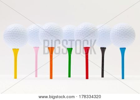 White golf balls and different tees on the white background. Funny golf concept.