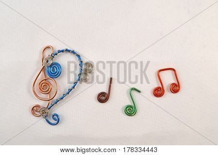 Bass clef treble clef and music notes made from colorful wires.