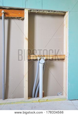 Repair and installation of plumbing faucets pipes tubes sewer water in the bathroom. Prepare for bath tub installation.