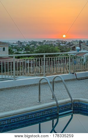 Swimming pool and sunset over village and sea on horizon