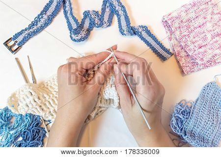 Knitting in woman hands. Hand Crochet.  Female hand knit hook. Top view. Needlework