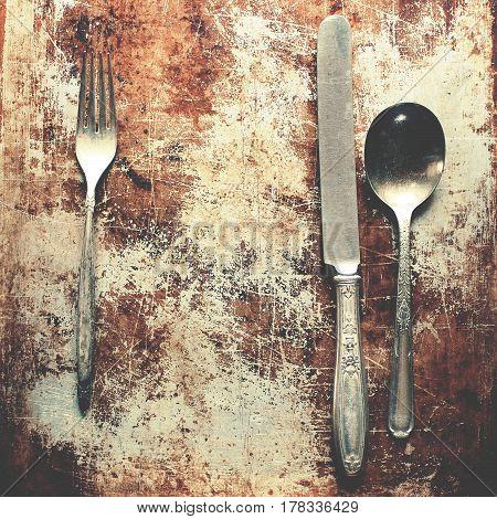 Vintage tarnished silverware against tarnished metal background.