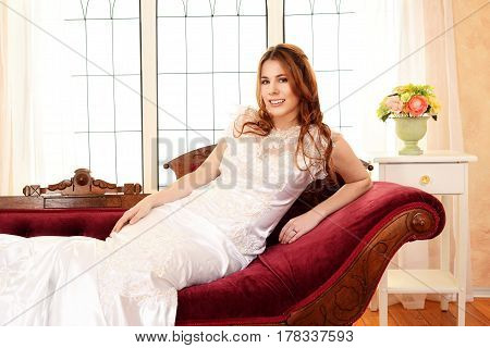 portrait of bride relaxing on fainting couch