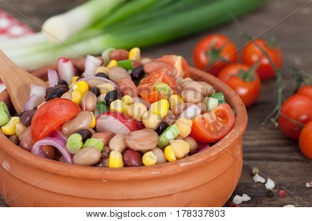 Vegetarian salad with red and black beans, chickpeas and corn in clay bowl