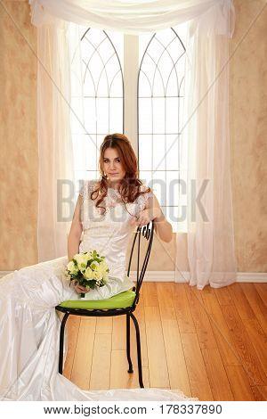 portrait of bride sitting on metal chair by window