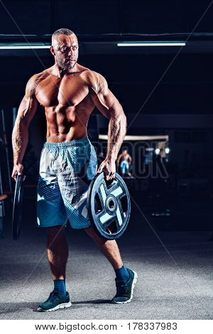 power athletic guy standing in gym with dumbbells