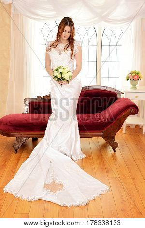 young bride with bouquet standing in front of large window