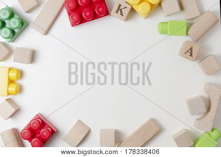 Kids toys background with copy space for text. Bright plastic construction blocks and wooden cubes on white background as frame. Top view. Flat lay