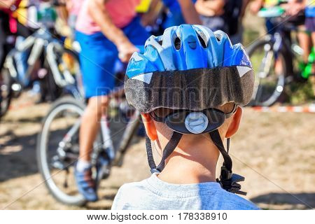 Boy In Helmet On Background а Group Of Cyclists Organized A Summer Arrival On Bikes On The Road. The