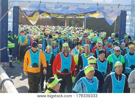 STOCKHOLM SWEDEN - MAR 25 2017: Crowd of runners men and woman in blue vests and yellow bandeau waiting for the start in the Stockholm Tunnel Run Citybanan 2017. March 25 2017 in Stockholm Sweden