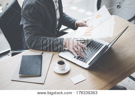 Elegant businessman working at sunny office on laptop while sitting at the wooden table.Man holding documents in his hands.Blurred background