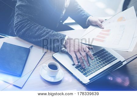 Elegant businessman working at sunny office on laptop while sitting at the wooden table.Man holding finace reports in hands.Blurred background.Visual effects