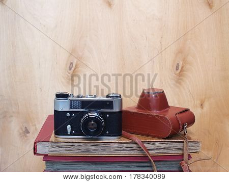 Vintage old film photo-camera with leather case on wooden background