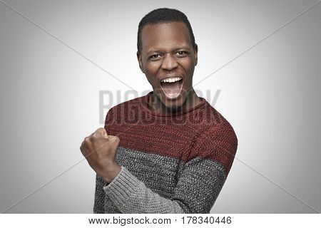 Headshot of happy successful African American male in casual knitted sweater raised his fist and screaming with winning expression celebrating success. Life perception and achievement concept.