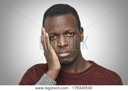 Tooth ache concept. Indoor headshot of young African American male feeling pain holding his cheek with hand. Black man suffering from bad toothache looking at camera with painful expression.