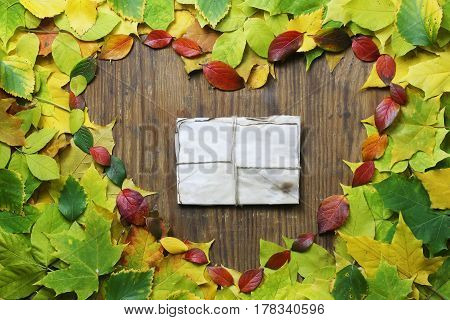 composition of yellowed and reddened maple leaves on the table Autumn time