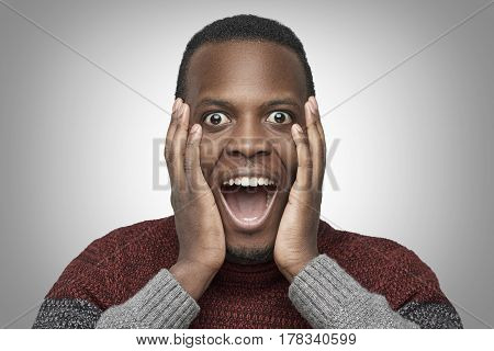 Close up portrait of excited African American male with shocked and surprised face looking and screaming at camera with big eyes and mouth wide open holding hands on his cheeks. Wow face concept.
