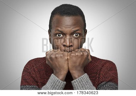 Portrait of scared young African American man dressed in sweater keeping hands in fists holding them in front of his face looking at camera with shocked and frightened expression. Fear concept.