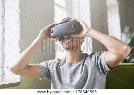 Smiling man using oculus rift headset experiencing virtual reality while playing video game sitting on green sofa at home. European male holding with hands 3d glasses in modern coworking studio