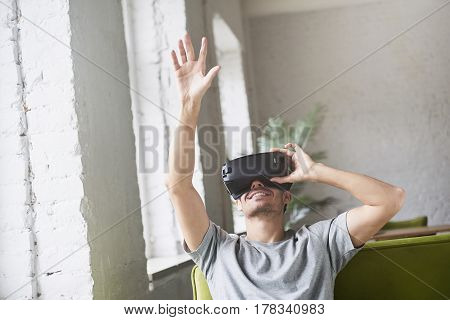 Young caucasian male catch something in the air play innovative virtual reality headset for mobile gaming applications sitting on sofa at home. Use mobile games apps with innovative glasses.