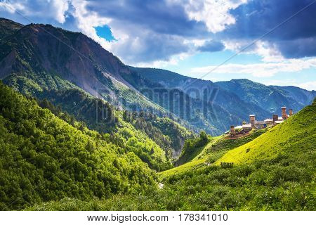 A nice small Georgian village with towers situated among high mountains covered with forests meadows with flowers and river. Upper Svaneti Europe. Happy lifestyle. Beautiful universe.