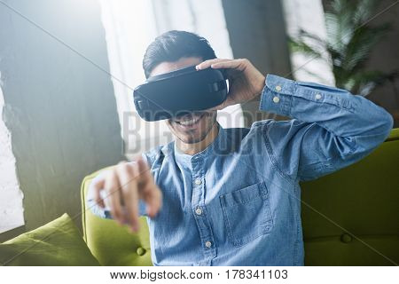 VR glasses. Smiling young caucasian in blue denim shirt man in virtual reality headset or 3d glasses pointing with finger in the air playing video game sitting on sofa at home. Lens flares effect