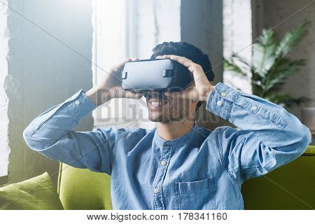 Smartphone using with VR headset. Astonished young caucasian male holding oculus rift headset on hands experiencing virtual reality while playing video game or waching movie. Lens flares effect