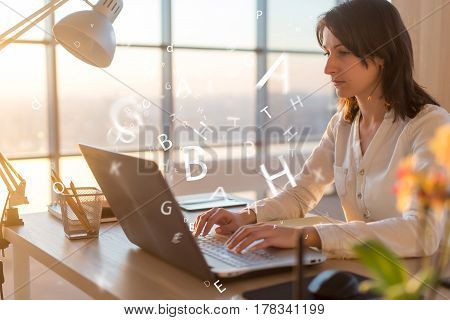 Woman at workplace using laptop working, typing, surfing the internet.