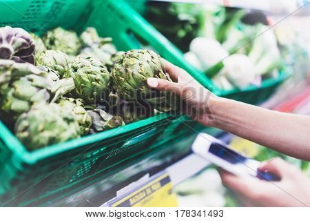 Young woman shopping healthy food in supermarket blur background. Female hands buy products artichoke using smartphone in store. Hipster at grocery using smartphone. Person comparing price of produce