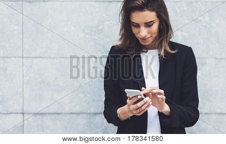 Portrait young businesswomen in black suit using smartphone isolated on background concrete gray wall mockup pretty hipster manager holding mobile gadget girl smiletexting message connect