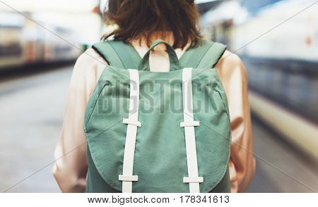 Enjoying travel. Young pretty woman waiting on the station platform with backpack on background electric train. Tourist texting message and plan route of railway railroad transport concept