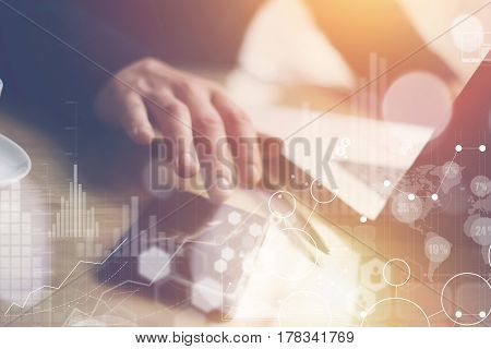 Concept of digital screen, virtual connection icon, diagram, graph interfaces.Businessman working at sunny office on laptop and smartphone while sitting at the wooden table.Sunlights effects.Blurred
