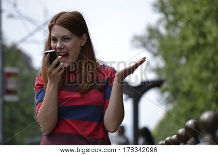 Angry girl yelling on a phone call at the city street