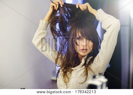 Beautiful Woman In Front Of The Mirror Doing Hair