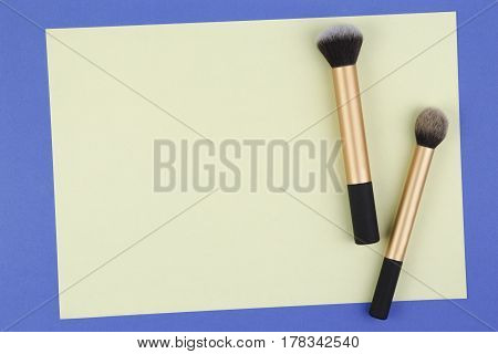 Make up brushes with yellow blank paper on blue background. Top view. Flat lay. Copy space for text