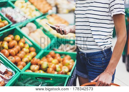 Young woman shopping healthy food in supermarket blur background. Female hands buy products tomato using smartphone in store. Hipster at grocery using smartphone. Person comparing price of produce