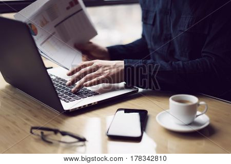 Elegant businessman working at sunny office on laptop while sitting at the wooden table.Man holding paper reports in hands.Blurred background