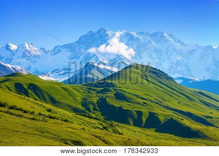 The nice view to the landscape of high mountains in the sunny day is opened from the green valley covered with grass. Upper Svaneti Georgia Europe. Happy lifestyle. Beautiful universe.